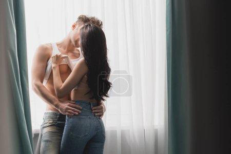 Photo pour Focus sélectif de femme sexy décoller chemise sans manches de petit ami musclé tout en embrassant près de la fenêtre - image libre de droit