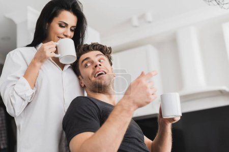 Selective focus of handsome man holding cup of coffee near smiling girlfriend in shirt