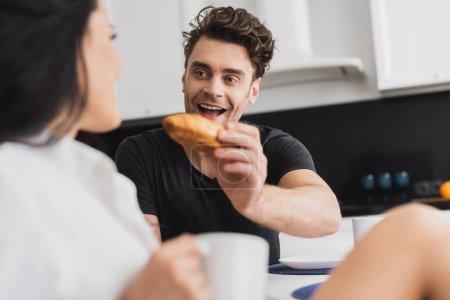 Photo pour Concentration sélective de l'homme positif tenant croissant près de petite amie avec tasse de café - image libre de droit