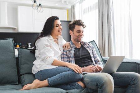 Photo pour Femme souriante assise près beau petit ami en utilisant un ordinateur portable sur le canapé à la maison - image libre de droit