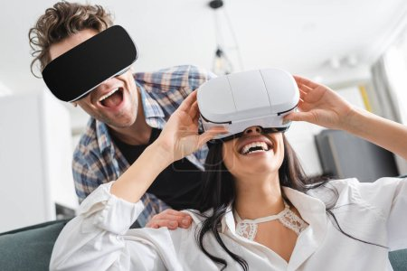 Photo for Cheerful couple using virtual reality headsets at home - Royalty Free Image
