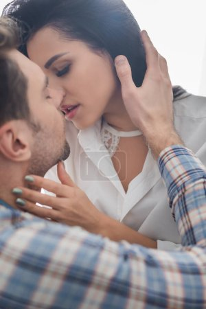 Selective focus of beautiful woman kissing and touching neck of boyfriend