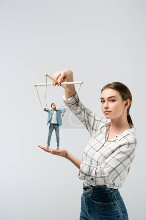 female puppeteer holding male marionette isolated on grey
