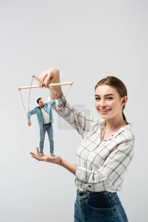 Photo for Smiling female puppeteer holding male marionette isolated on grey - Royalty Free Image