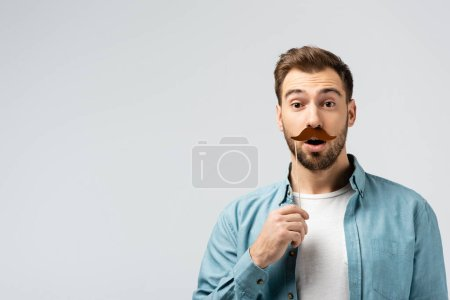 shocked young man with fake mustache on stick isolated on grey