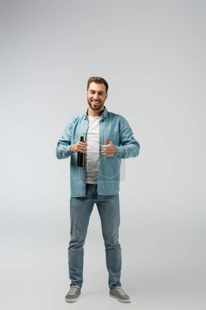 Lächelnder junger Mann mit Bierflasche zeigt Daumen in die Höhe