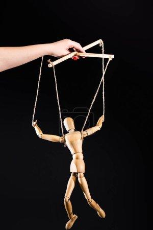 Photo pour Vue recadrée du marionnettiste tenant une marionnette en bois isolée sur du noir - image libre de droit