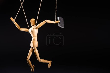 wooden marionette on strings with suitcase isolated on black