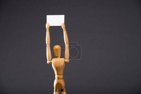 Photo pour Marionnette en bois tenant une pancarte vierge sur fond noir - image libre de droit