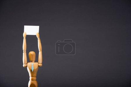 Photo pour Marionnette en bois attachée tenant une pancarte vierge sur fond noir - image libre de droit