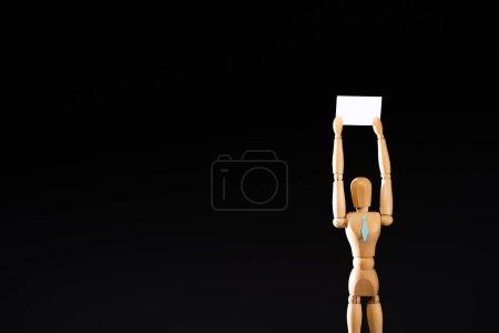 Photo pour Marionnette en bois en cravate tenant une pancarte vierge isolée sur noir - image libre de droit