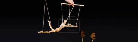 cropped view of puppeteer holding wooden marionette on strings near currency signs isolated on black, panoramic shot