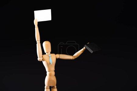 Photo pour Marionnette en bois en cravate avec valise tenant une pancarte vierge isolée sur noir - image libre de droit