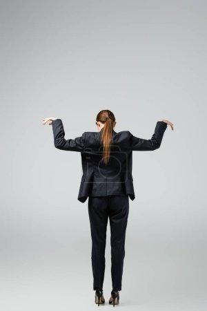 Photo pour Vue arrière de marionnette femme d'affaires en costume posant isolé sur gris - image libre de droit