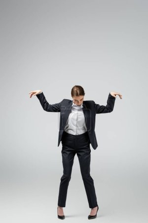 businesswoman marionette in suit posing isolated on grey