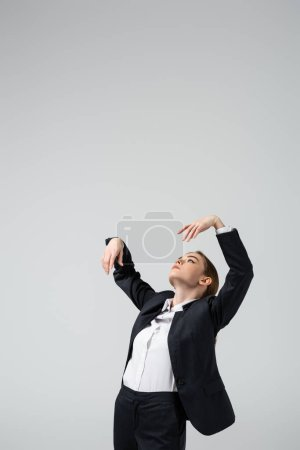 businesswoman marionette in suit posing with raised hands isolated on grey