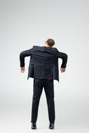 back view of businessman marionette in suit posing with hands down isolated on grey