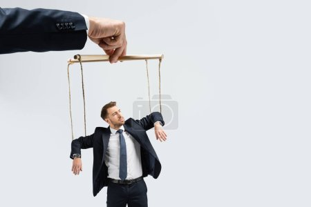 cropped view of puppeteer holding businessman marionette on strings isolated on grey