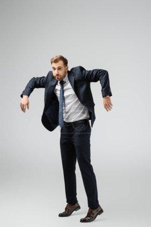 Photo pour Homme d'affaires marionnette en costume posant avec les mains vers le bas isolé sur gris - image libre de droit