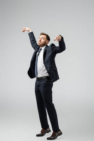 businessman marionette in suit posing with raised hands isolated on grey