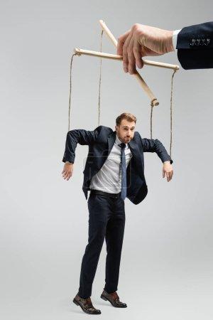 Photo pour Vue recadrée d'un marionnettiste tenant une marionnette d'homme d'affaires sur des cordes isolées sur du gris - image libre de droit