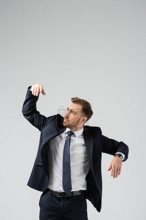 Photo pour Marionnette homme d'affaires en costume avec main levée isolée sur gris - image libre de droit