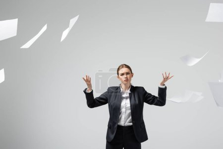 displeased businesswoman in suit throwing papers in air isolated on grey