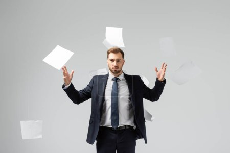 Photo for Displeased businessman in suit throwing papers in air isolated on grey - Royalty Free Image