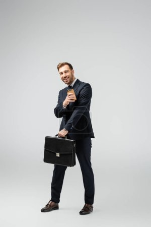 Photo for Happy businessman with leather suitcase and paper cup isolated on grey - Royalty Free Image