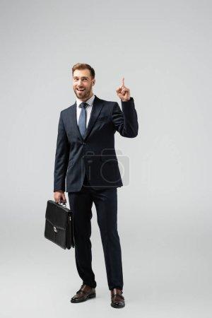 Lächelnder Geschäftsmann mit Lederkoffer zeigt vereinzelt auf grau