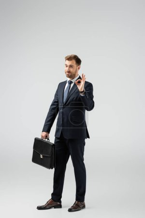 Photo for Businessman with leather suitcase showing ok sign isolated on grey - Royalty Free Image