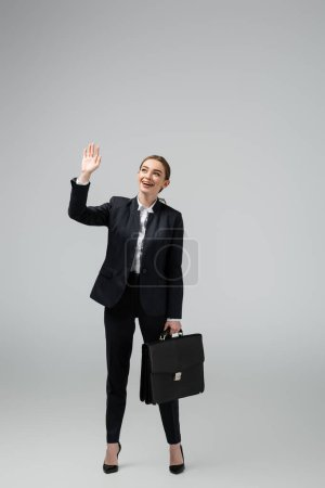 cheerful young businesswoman with leather suitcase waving hand isolated on grey