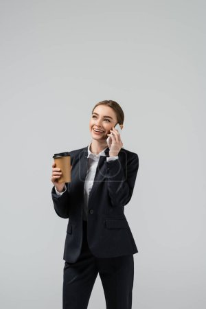 Photo for Happy young businesswoman with coffee to go talking on smartphone isolated on grey - Royalty Free Image
