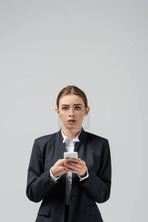 Photo for Sad young businesswoman using smartphone isolated on grey - Royalty Free Image