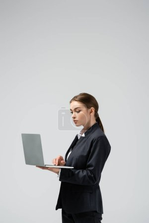 Photo for Serious young businesswoman using laptop isolated on grey - Royalty Free Image