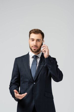 Photo for Handsome businessman in suit talking on smartphone isolated on grey - Royalty Free Image