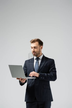 Photo for Handsome businessman in suit using laptop isolated on grey - Royalty Free Image