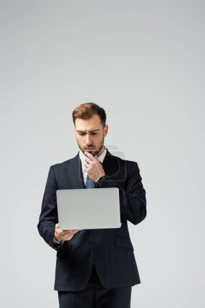 pensive handsome businessman in suit using laptop isolated on grey
