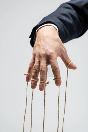 partial view of puppeteer with strings on fingers isolated on grey