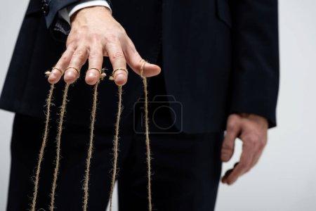 Photo pour Vue partielle du marionnettiste en costume avec des cordes sur les doigts isolés sur le gris - image libre de droit