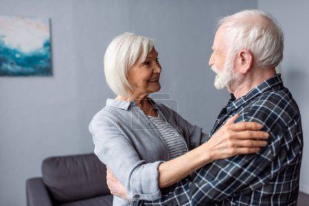 Photo for Happy senior couple smiling while hugging and looking at each other - Royalty Free Image