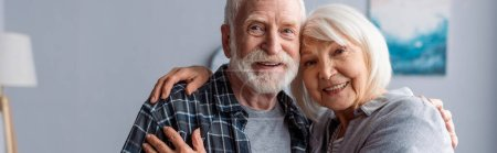 Photo for Horizontal image of happy senior couple smiling and embracing while looking at camera - Royalty Free Image