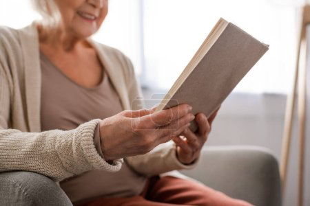 cropped view of senior woman sitting in armchair and reading book, selective focus