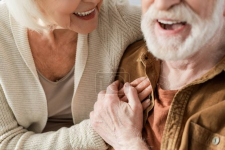 cropped view of laughing senior couple holding hands, selective focus