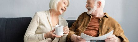 Photo for Horizontal image of senior woman with cup of tea and his husband with newspaper laughing while talking on sofa - Royalty Free Image