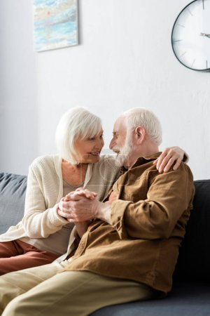 happy senior couple embracing and holding hands while looking at each other