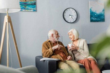 Photo pour Foyer sélectif de heureux couple de personnes âgées parlant tout en étant assis sur le canapé à la maison - image libre de droit