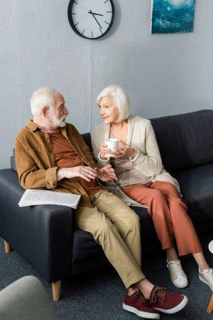 Photo pour Vue grand angle du couple de personnes âgées parlant assis sur le canapé - image libre de droit