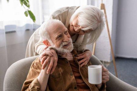 Photo pour Femme souriante étreignant mari aîné heureux assis avec une tasse de thé - image libre de droit