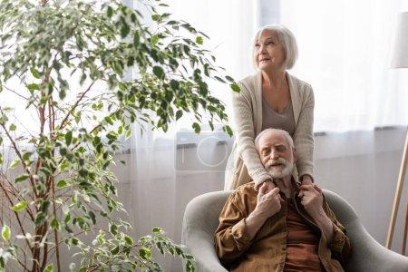 Photo pour Femme âgée tenant la main du mari aîné heureux assis sur le canapé avec les yeux fermés - image libre de droit